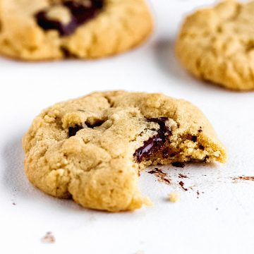 Single bitten cookie with chocolate chunks on a white marble surface