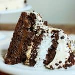 Large slice of chocolate meringue cake on white plate, earth colored background