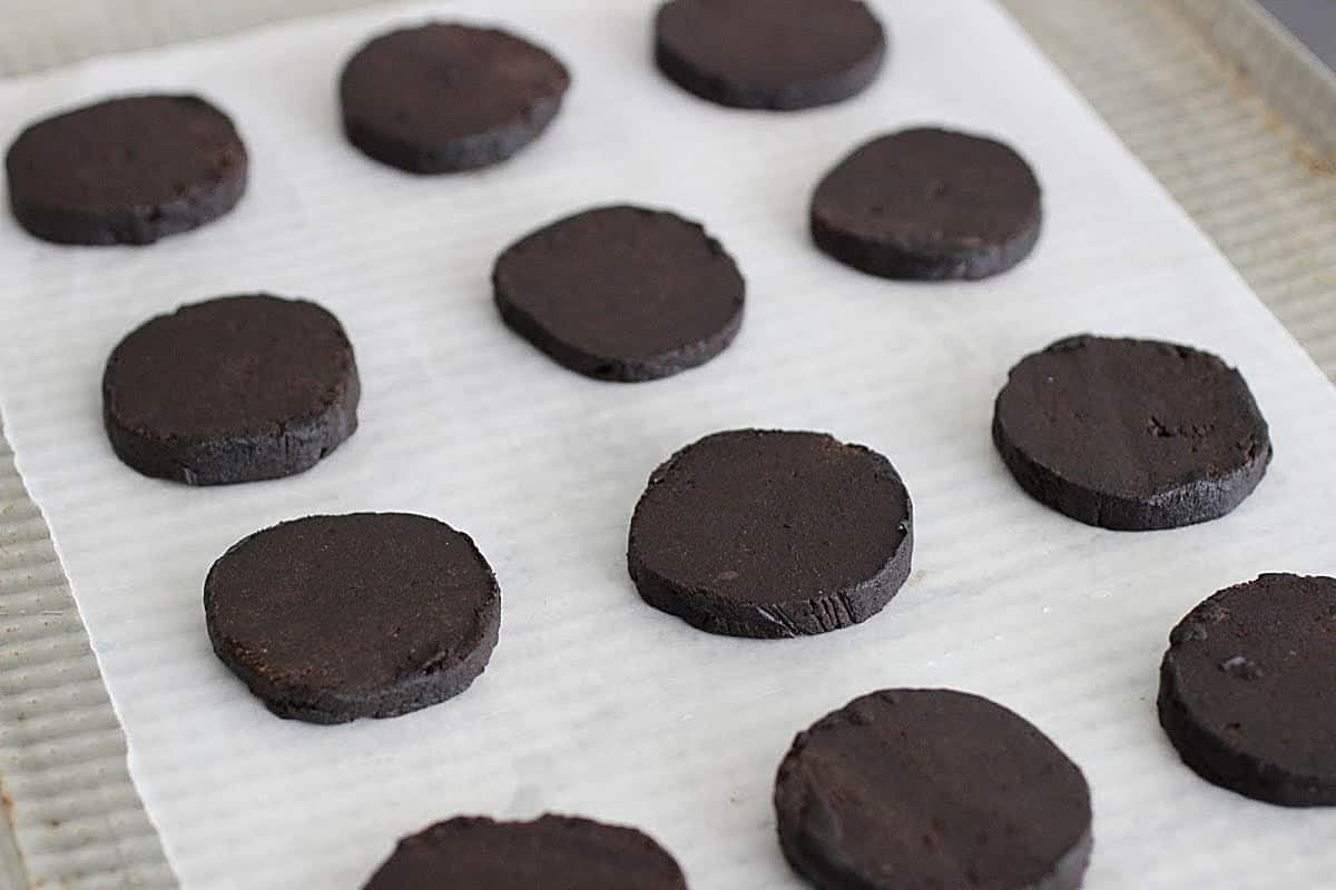 Three rows of unbaked chocolate cookies on parchment paper, metal cookie sheet