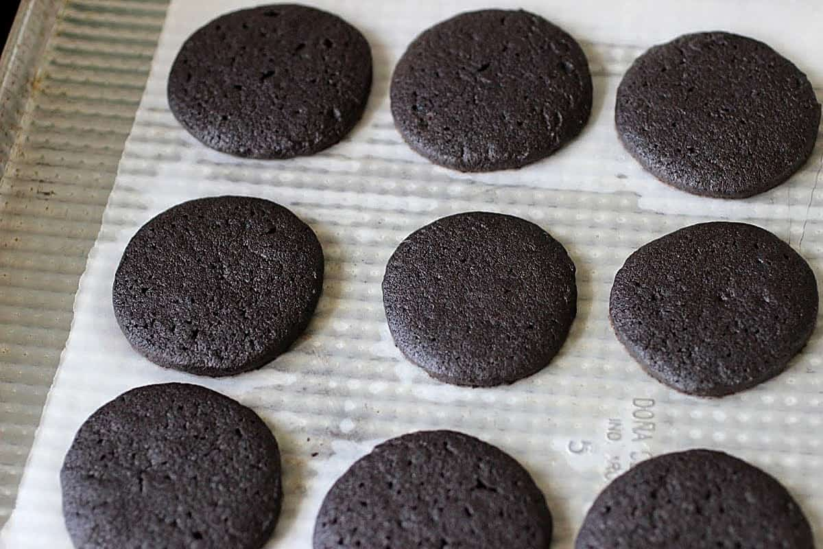 Baked chocolate cookies in three rows on a metal pan with white parchment paper