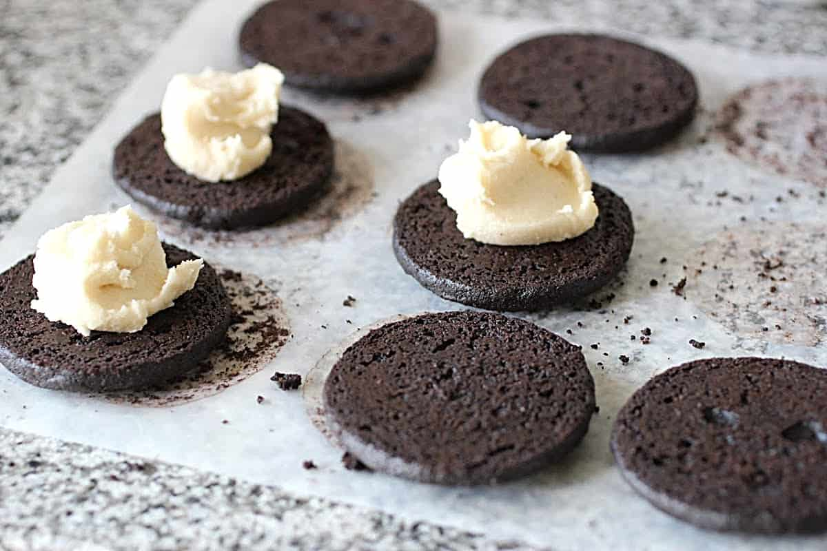 Chocolate cookie rounds on parchment paper on grey surface, some with mound of filling