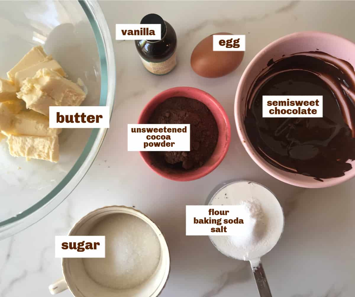 White surface with bowls of ingredients for chocolate cookies; image with text