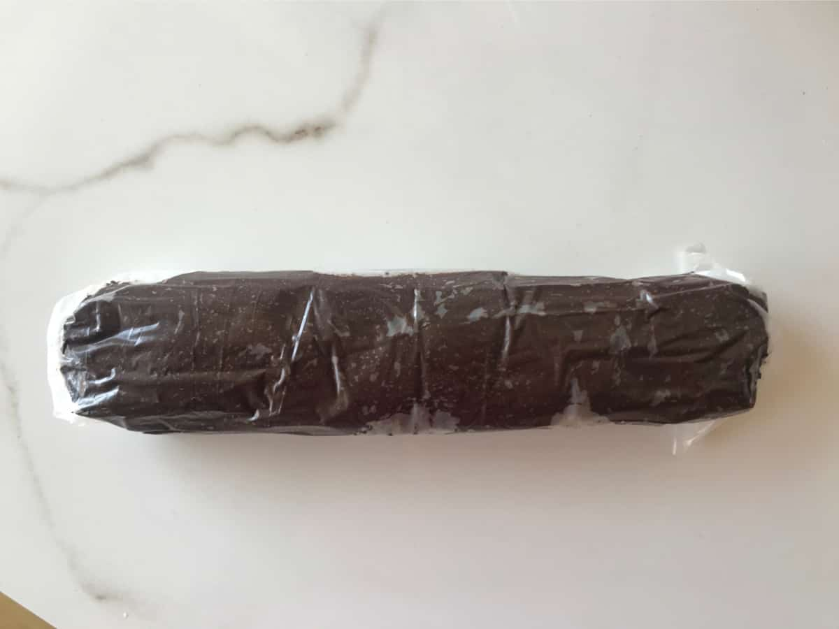 A log of chocolate cookie dough wrapped in plastic on a white marble surface