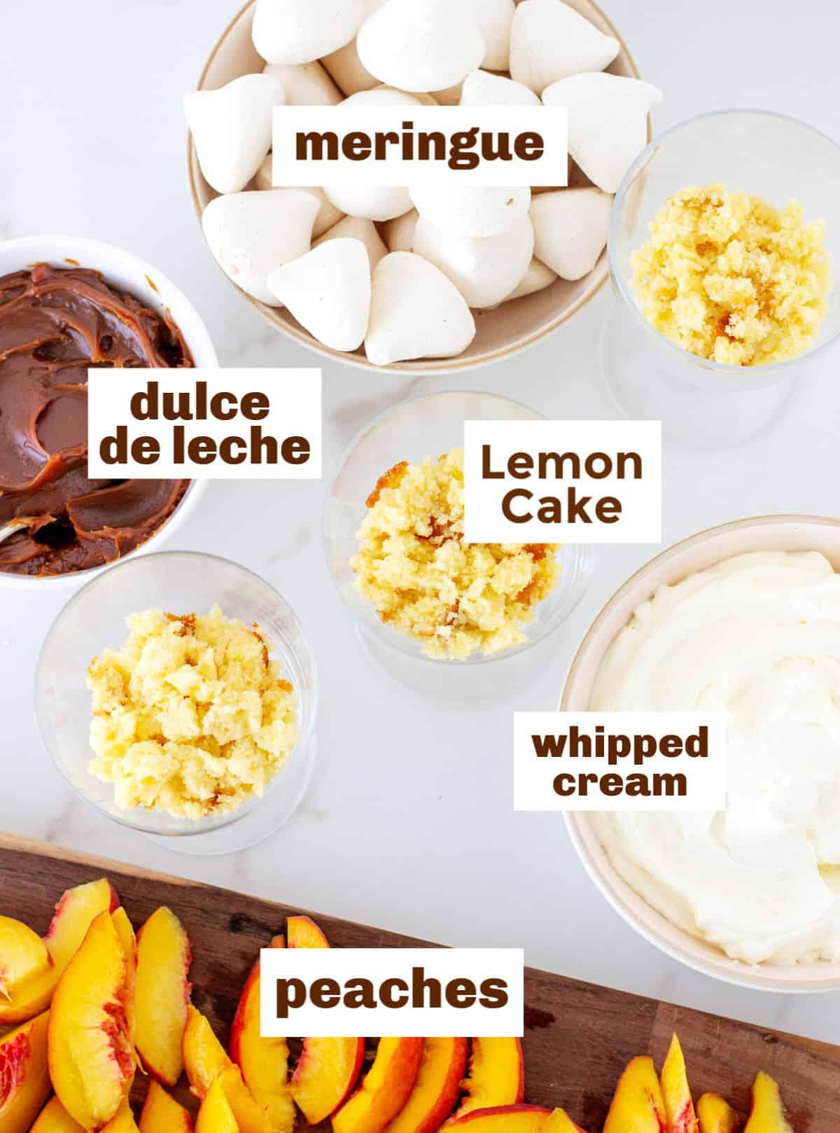 Peaches, cake, cream, meringue and dulce de leche in bowls on white surface