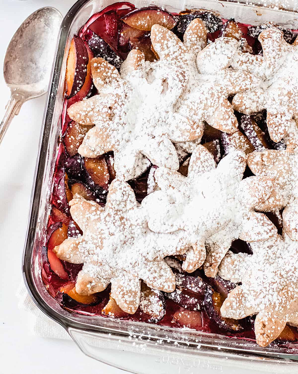 Partial photo of plum cobbler dusted with powdered sugar on a white surface, a silver spoon on the side