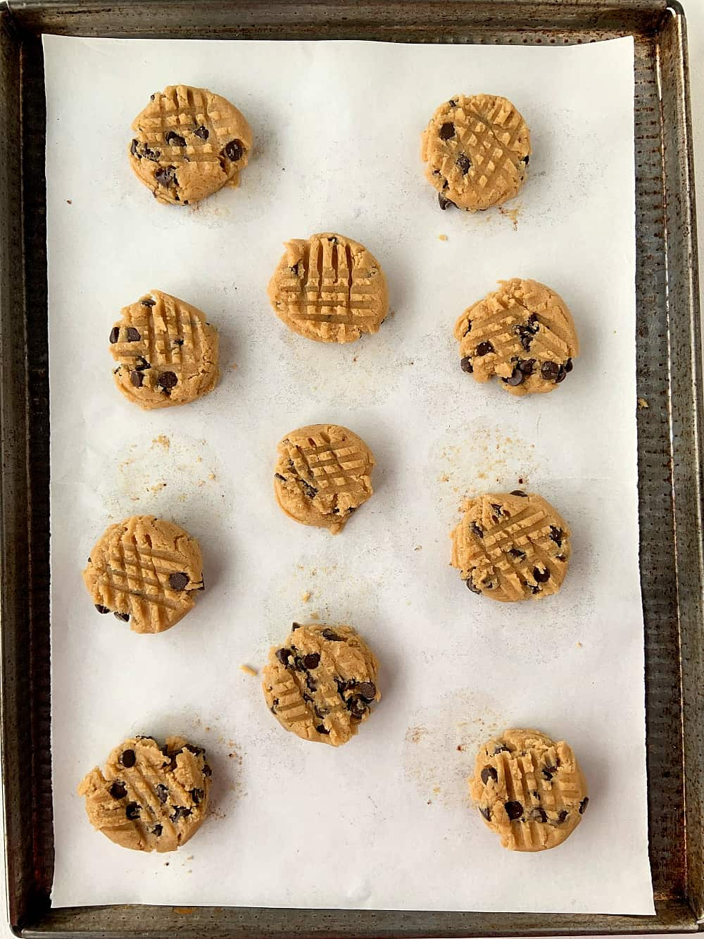 Metal cookie tray with unbaked almond butter cookies with chocolate chips on parchment paper.