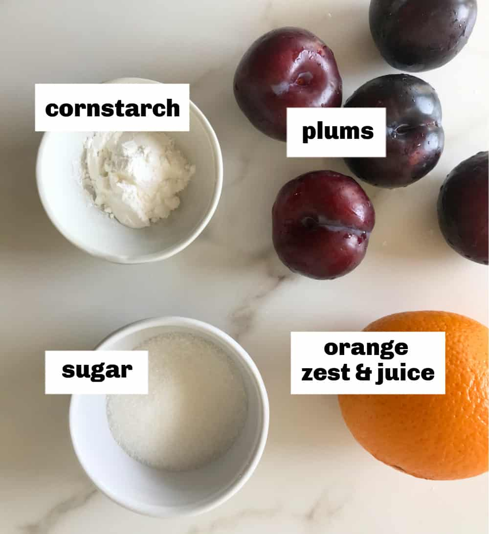 Plums, an orange and white bowls with ingredients for cobbler filling, image with text