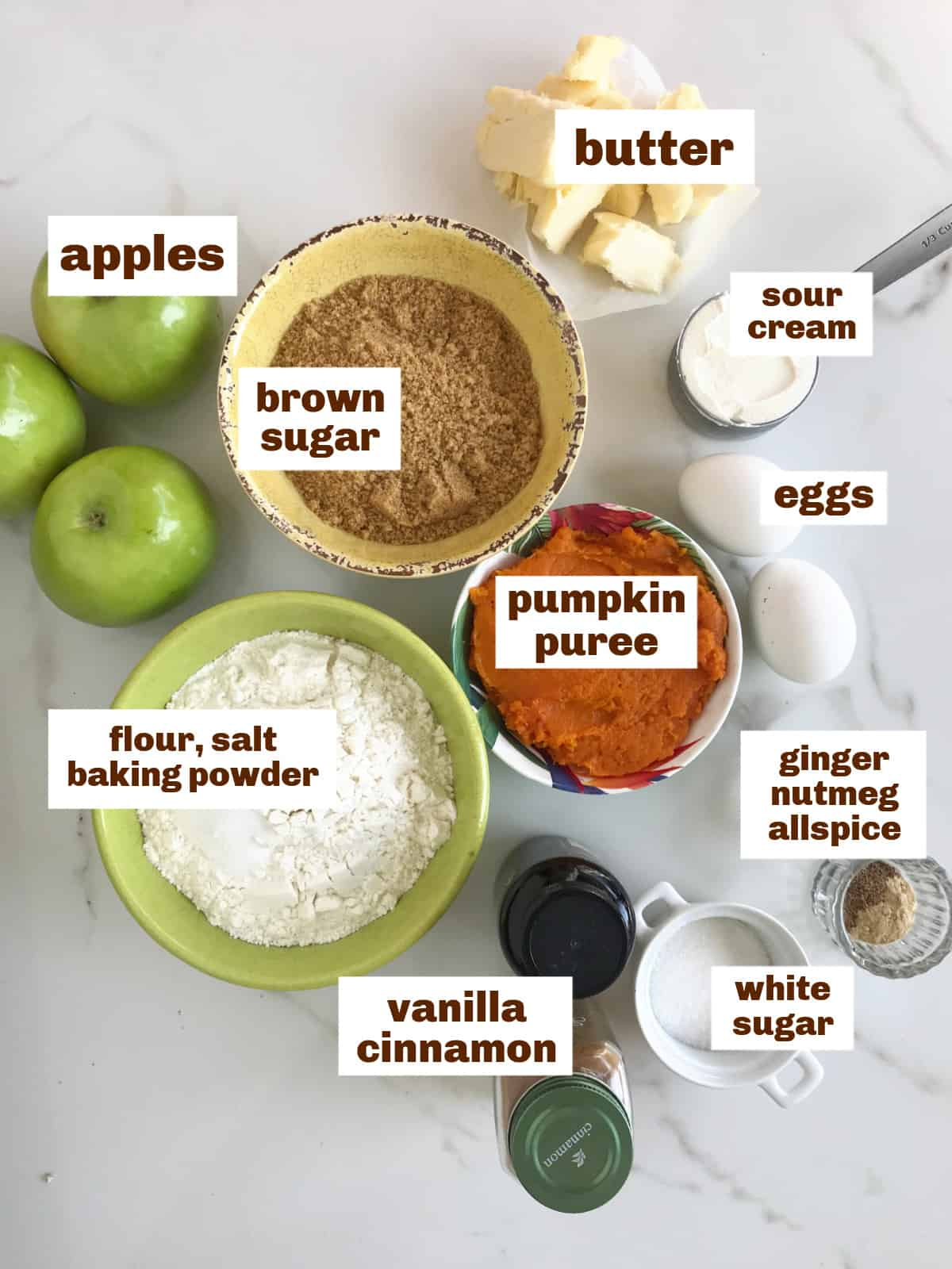 Different bowls with pumpkin apple cake ingredients, sugars, spices, whole apples