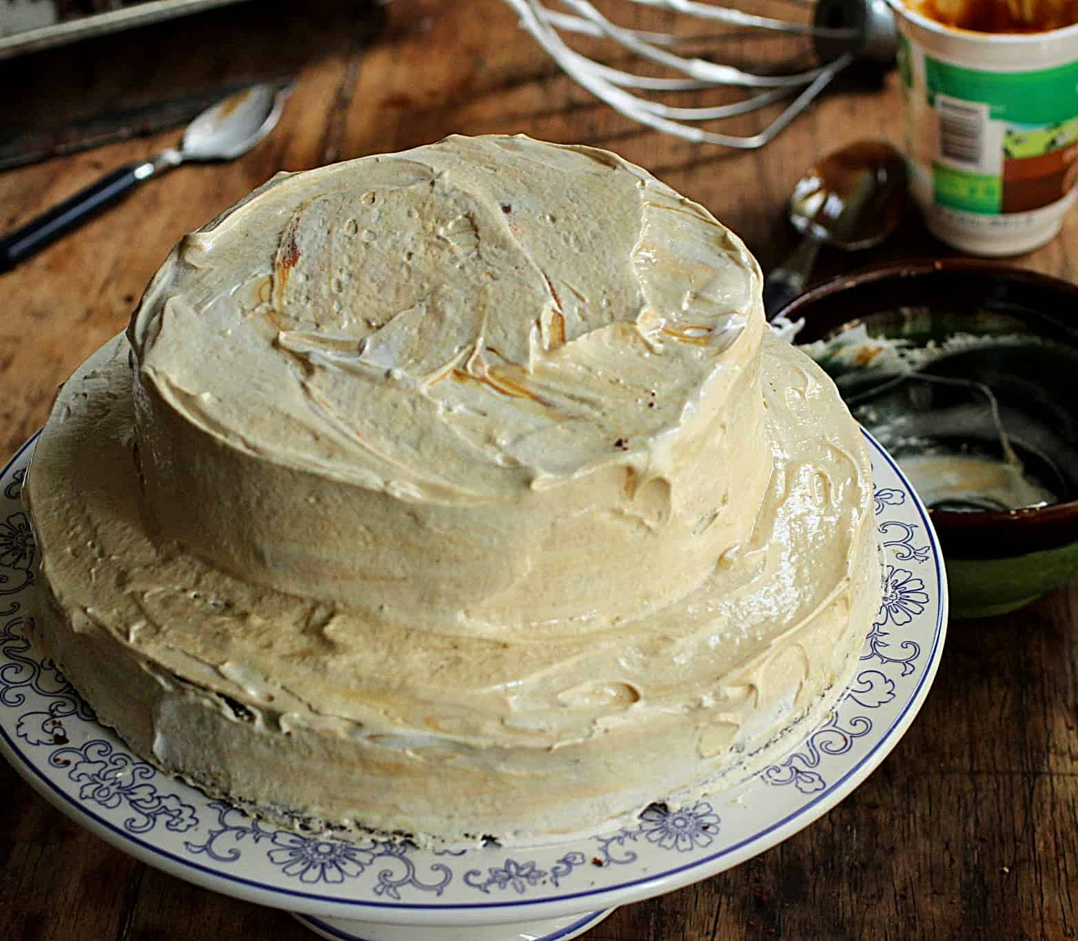 Whole meringue frosted cake on white blue cake stand, wooden table, utensils scattered around
