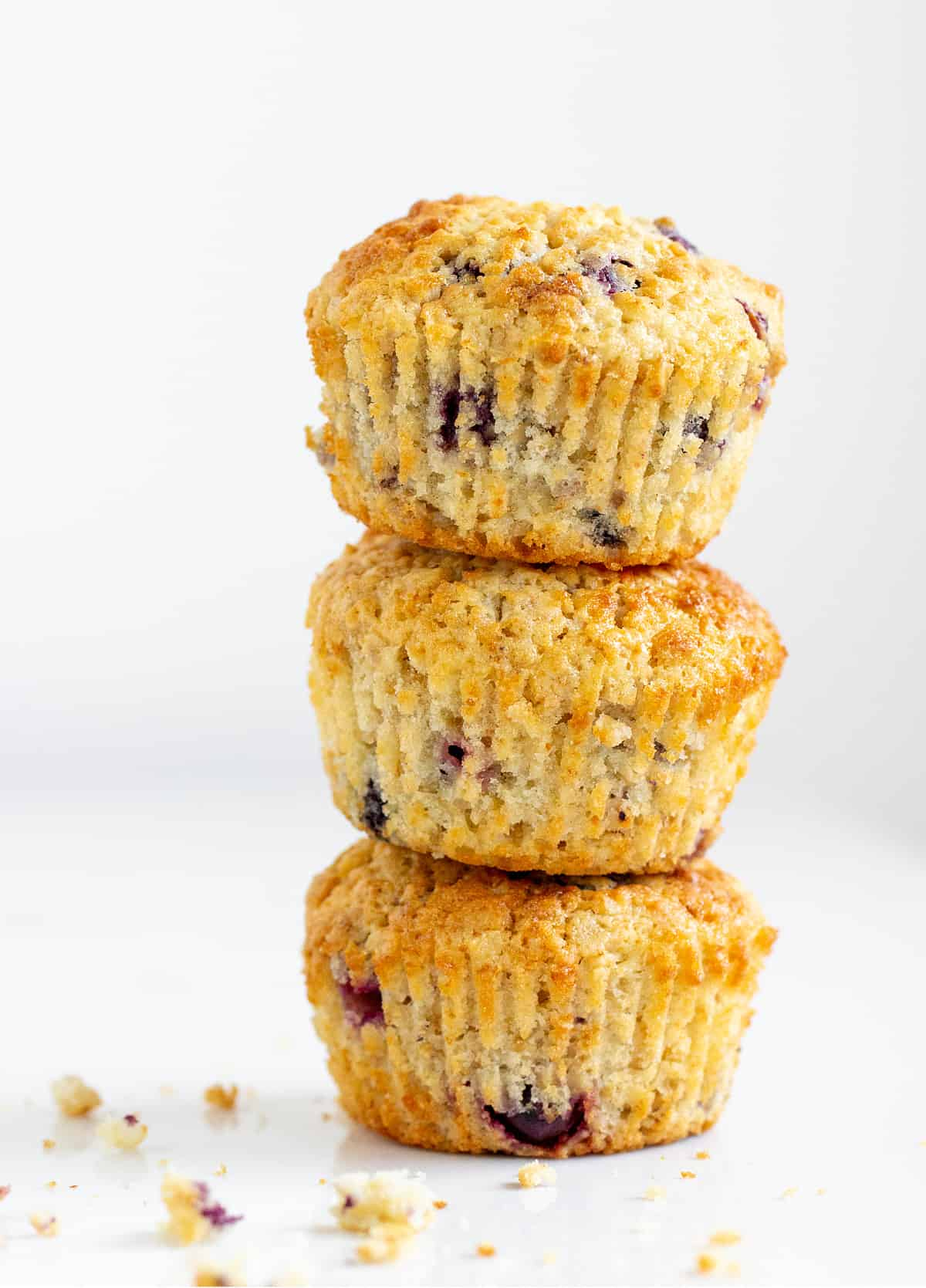 Stack of three golden colored muffins with blueberries, white background, some crumbs