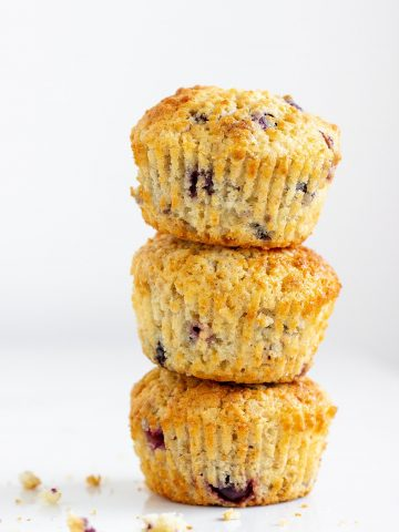 Stack of three golden colored muffins with blueberries, white surface and background