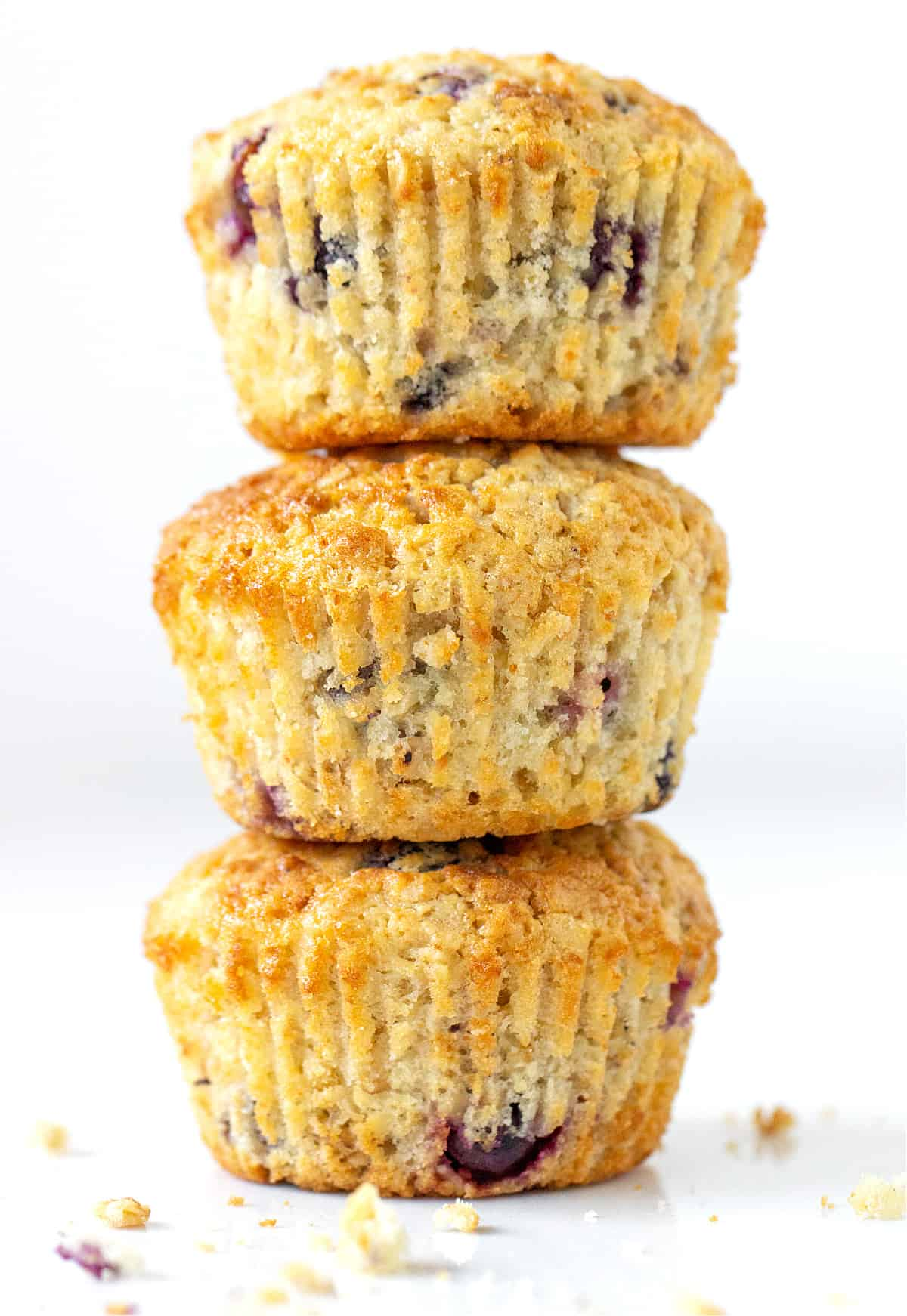 On a white background a stack of three blueberry muffins