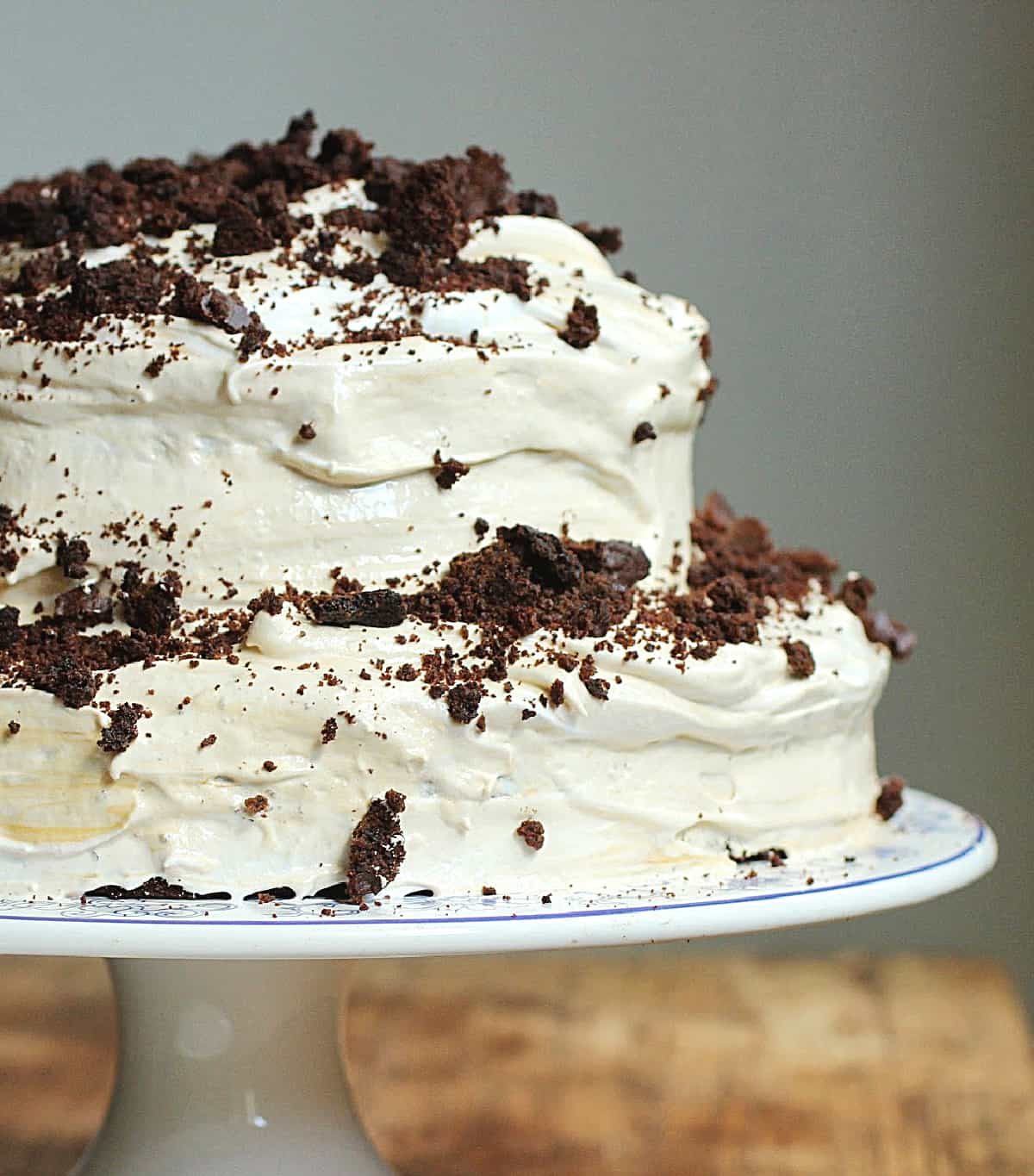 Partial view of whole cake on cake stand frosted with meringue and chocolate crumbs
