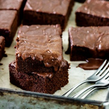 Stacked squares of glazed chocolate cake on metal square pan