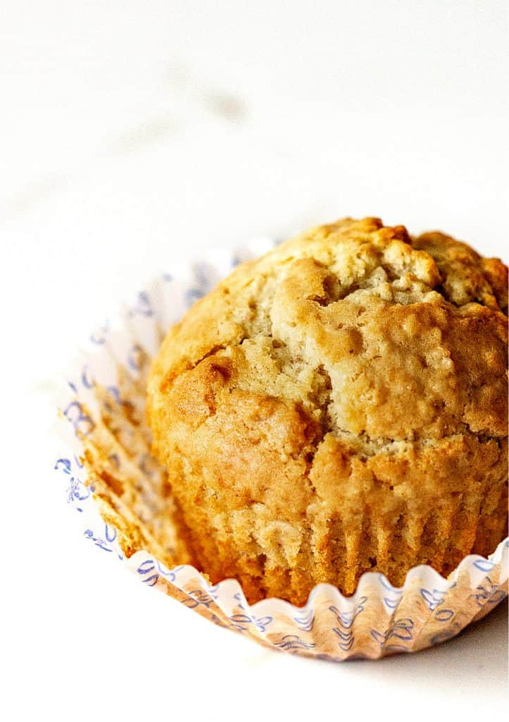 Single golden muffin on a white surface, opened paper cup
