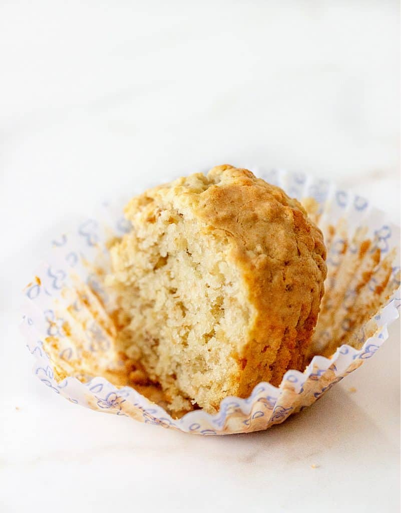 Half oatmeal muffin in light colored paper cup, white marble surface
