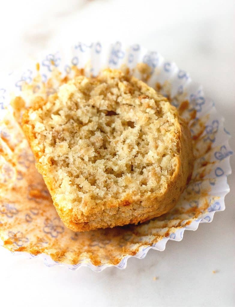 Half oatmeal muffin, cut side up, in an open paper liner on a white surface