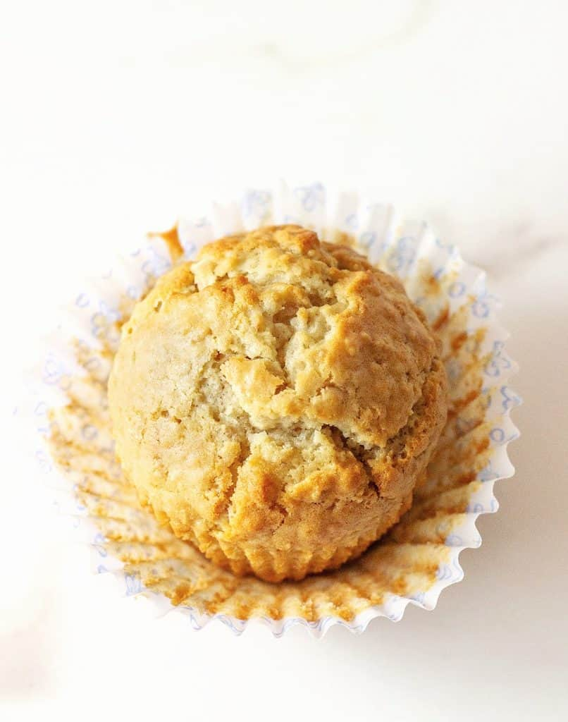 One golden colored muffin on an opened whitish paper cup, white surface