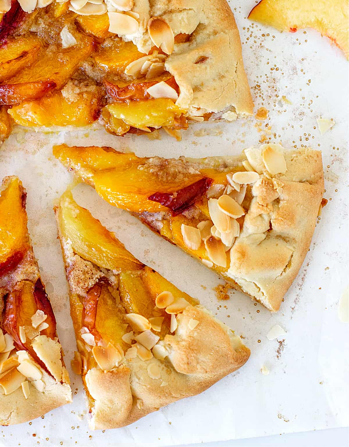 Half a free-form peach tart with almonds, white surface, cut slices