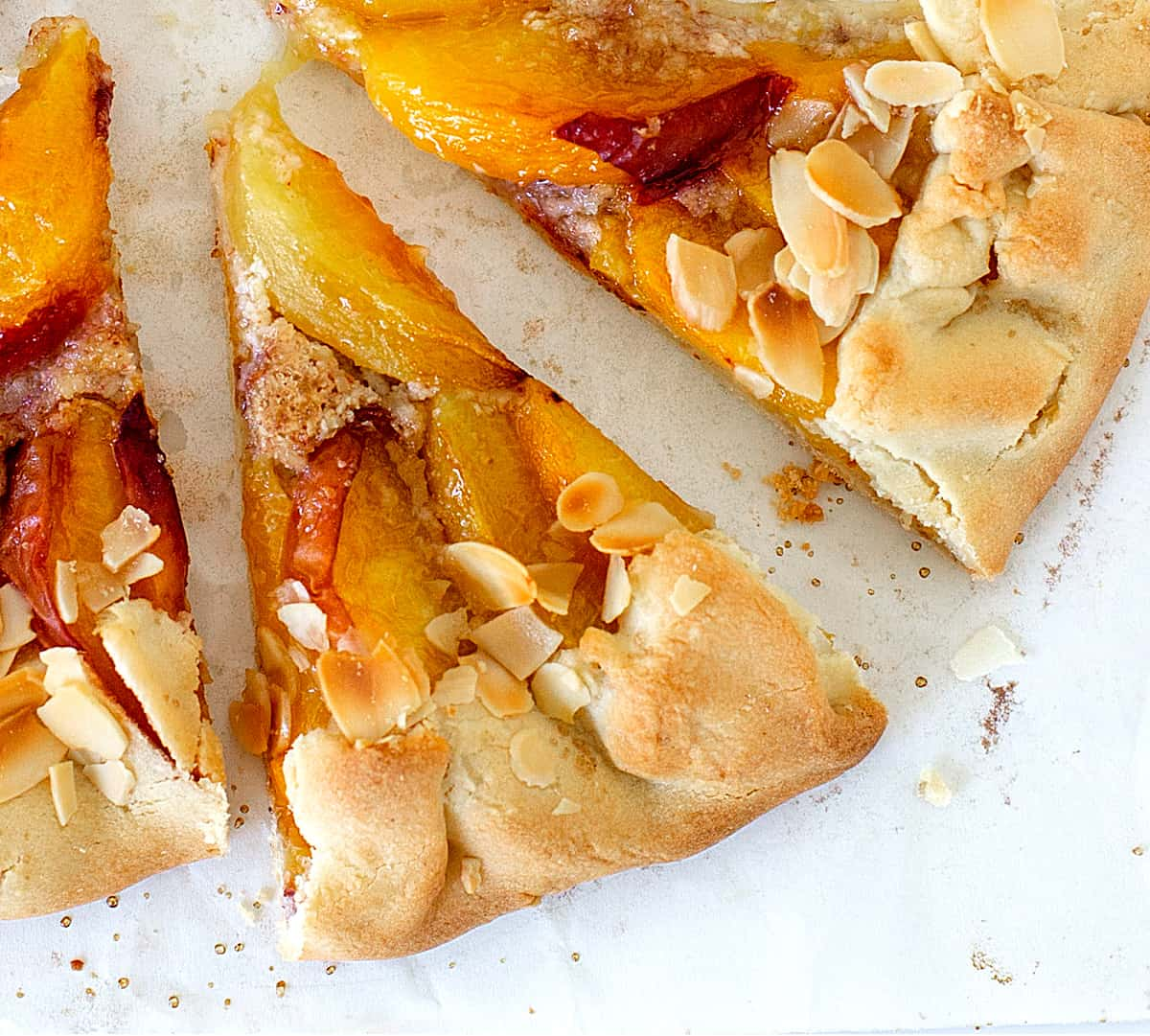 Close-up of two slices of baked peach galette on a white surface
