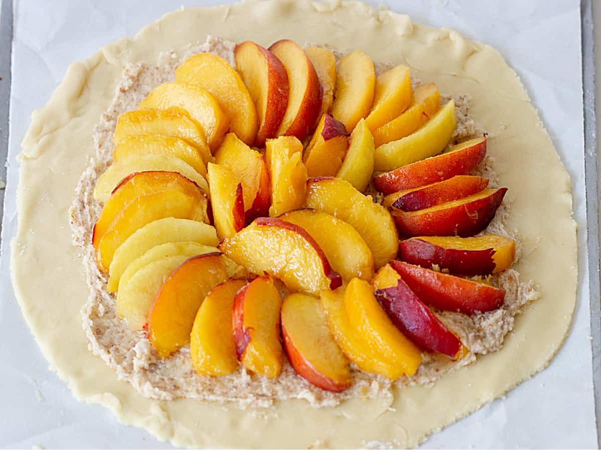 Round of pie dough on metal baking sheet with circle of peach slices and almond cream