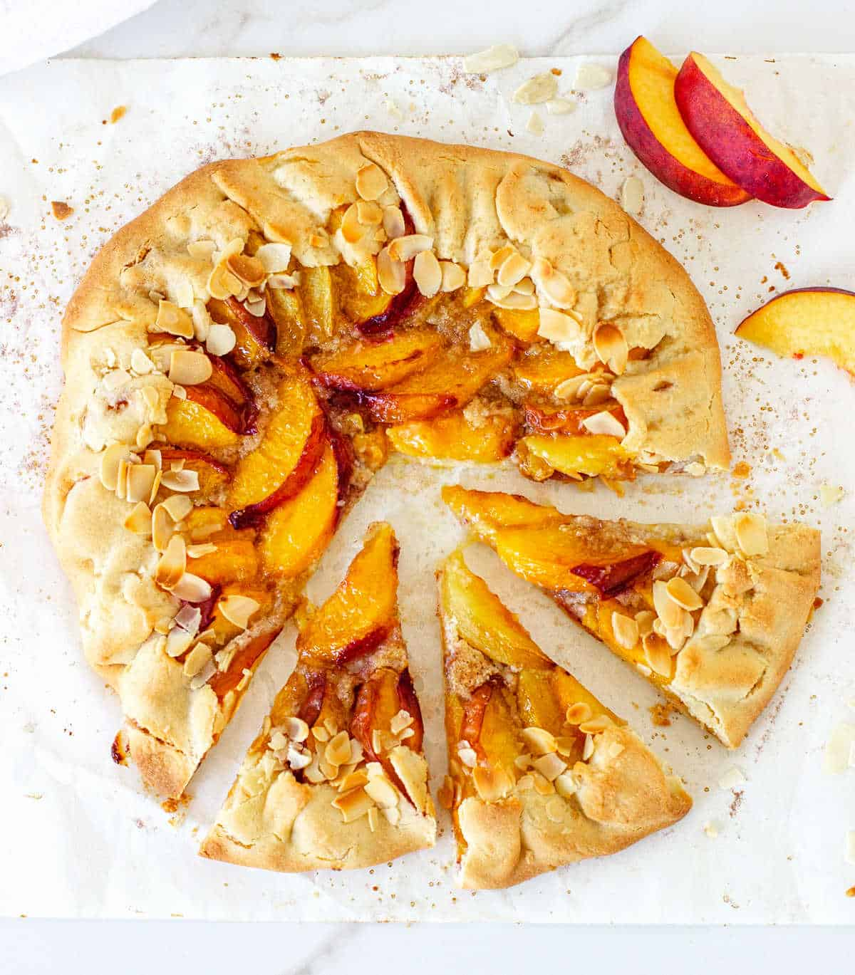 Whole baked peach galette on parchment paper, top view