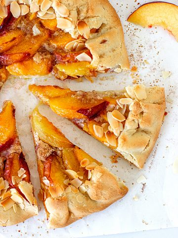 View of half peach galette slices on a white table