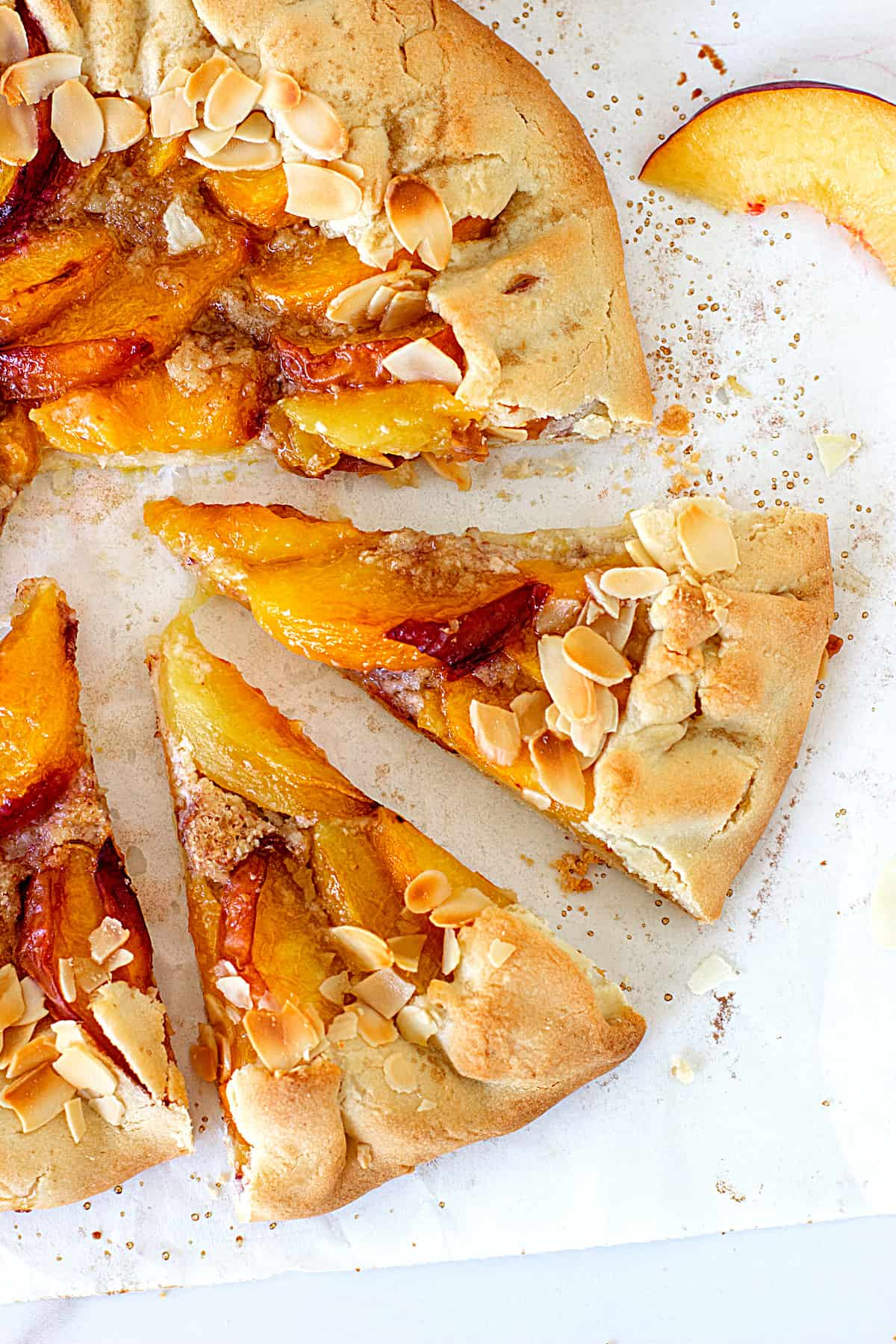 Two cut slices of a peach galette and rest of tart on a white surface, fresh peach slice