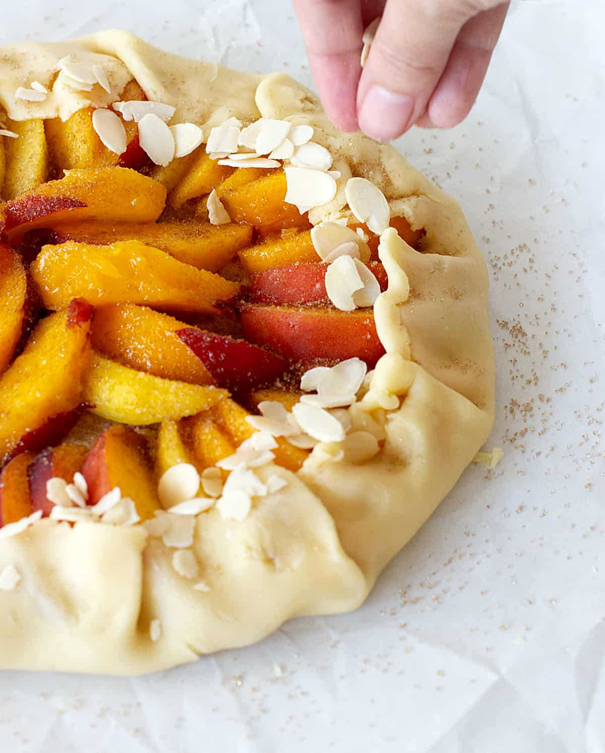 On a white surface an unbaked peach free-form tart, hand adding sliced amonds
