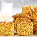 Stacked squares of carrot cake with walnuts, grey and white background