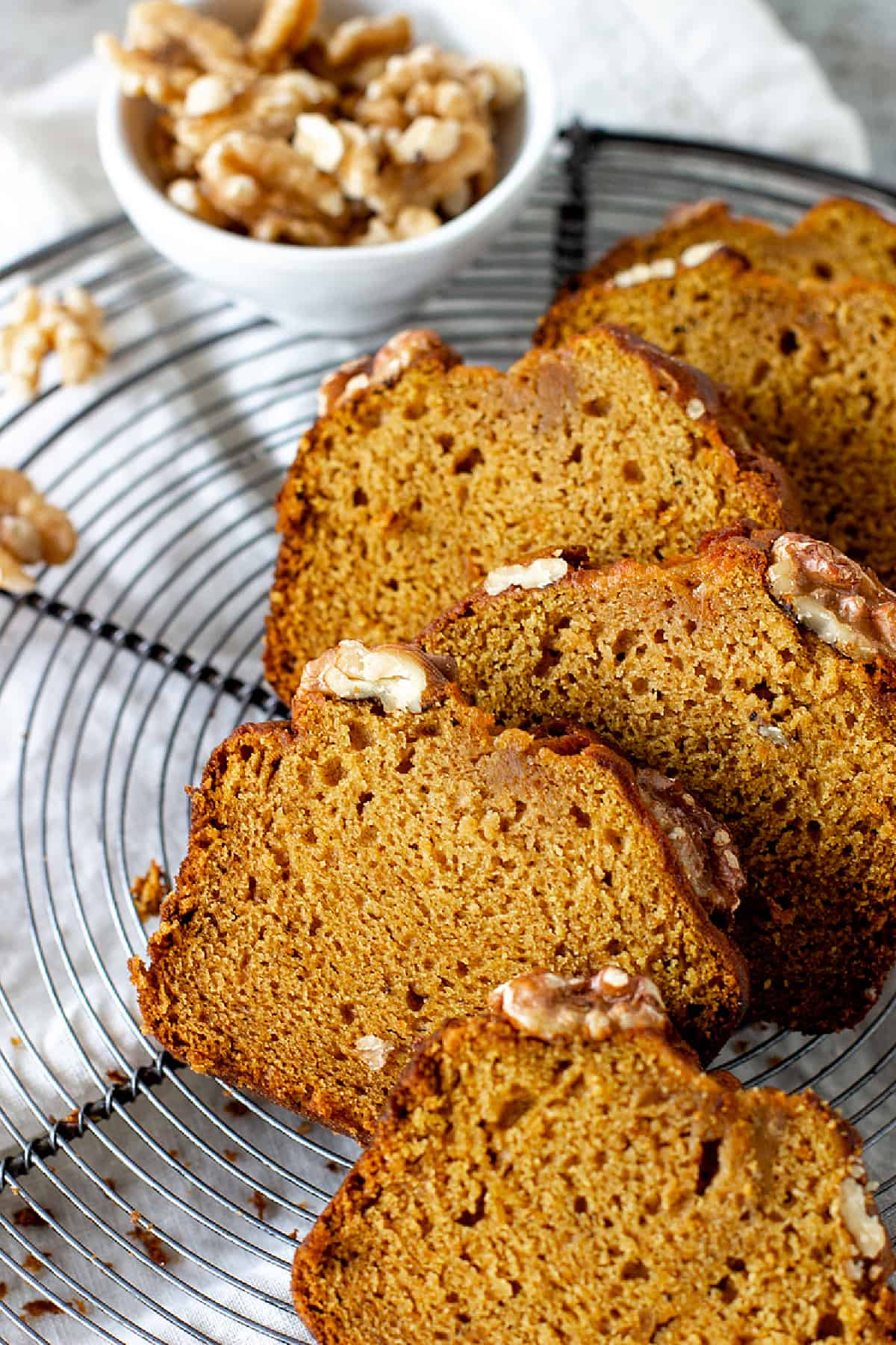 Five slices of pumpkin bread on round wire rack, small white bowl with walnuts, white cloth underneath