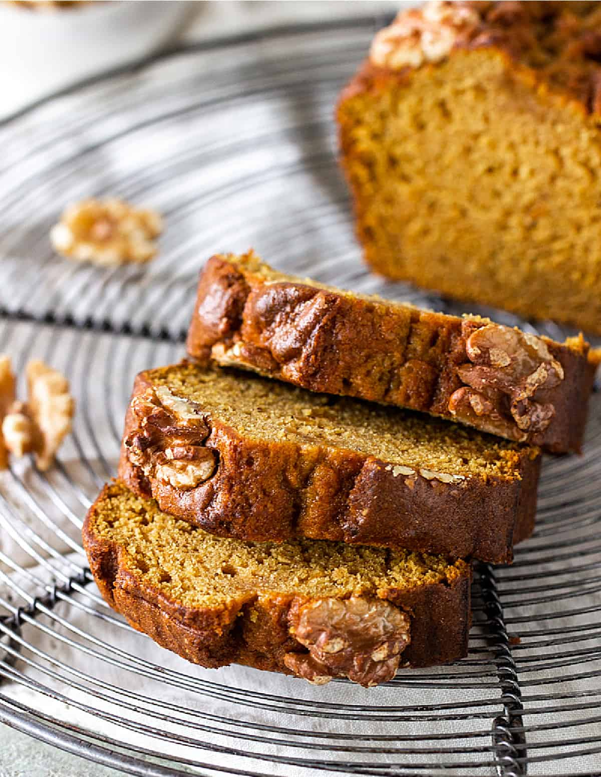 Three slices of golden pumpkin bread with walnuts, wire rack, loose walnut pieces, greyish surface