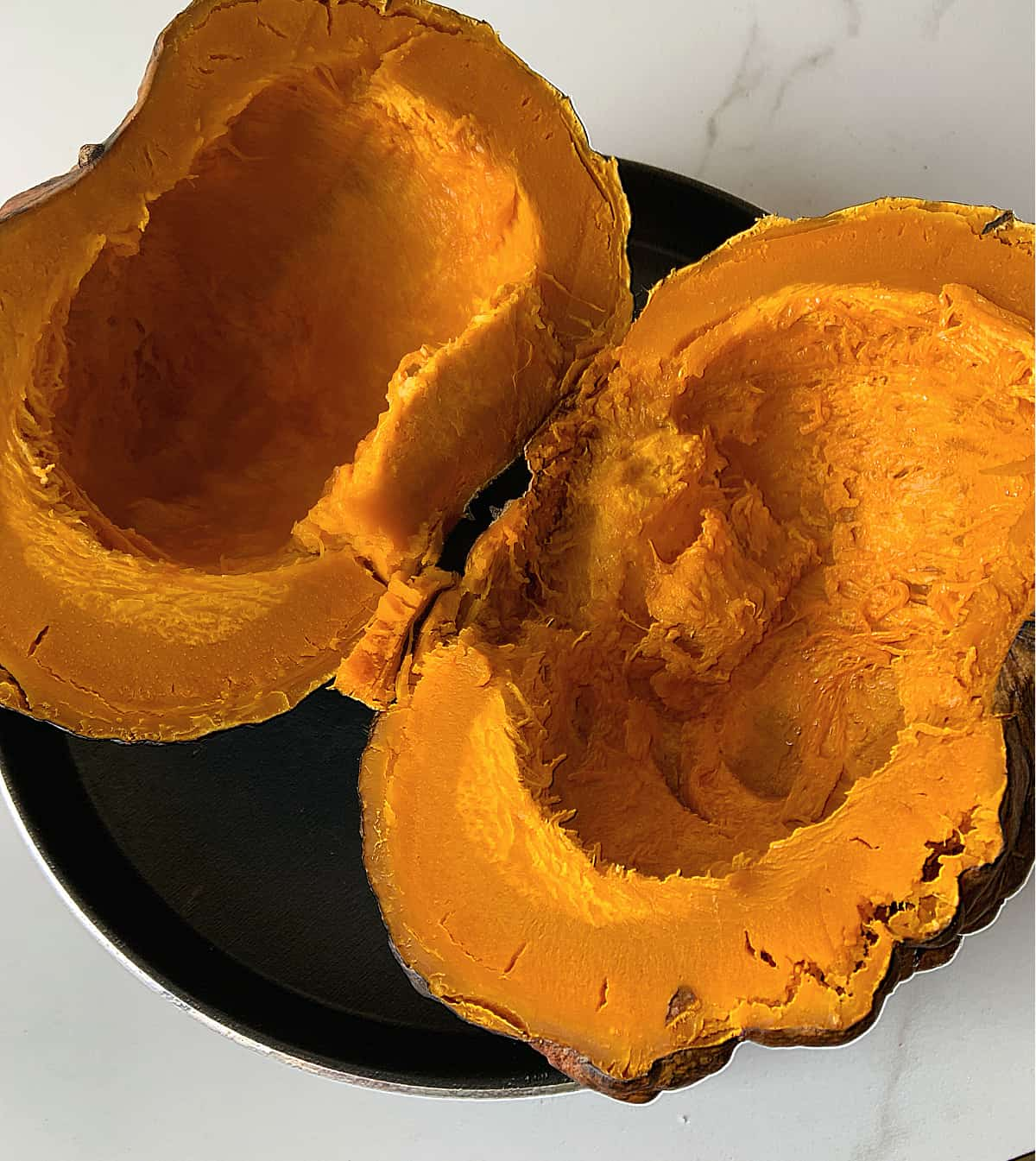 Whole baked pumpkin cut in half on black pan, white marble surface
