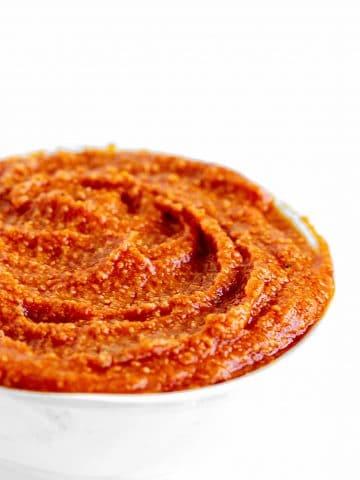 Reddish orange salsa romesco in a white bowl, white background