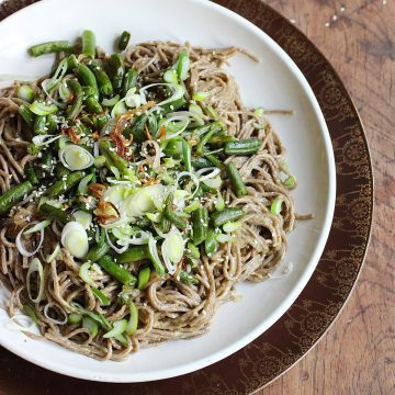Soba noodle salad topped with green beans on white plate, wooden table
