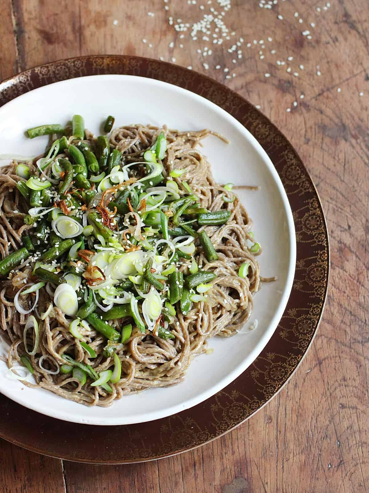 On a wooden table brown and white plates with noodle salad, green beans and shallots