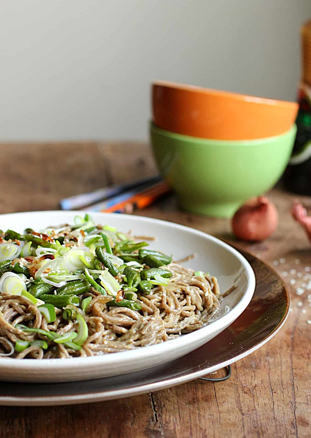 White plate with noodle salad with green beans, wooden table, colorful bowls in background