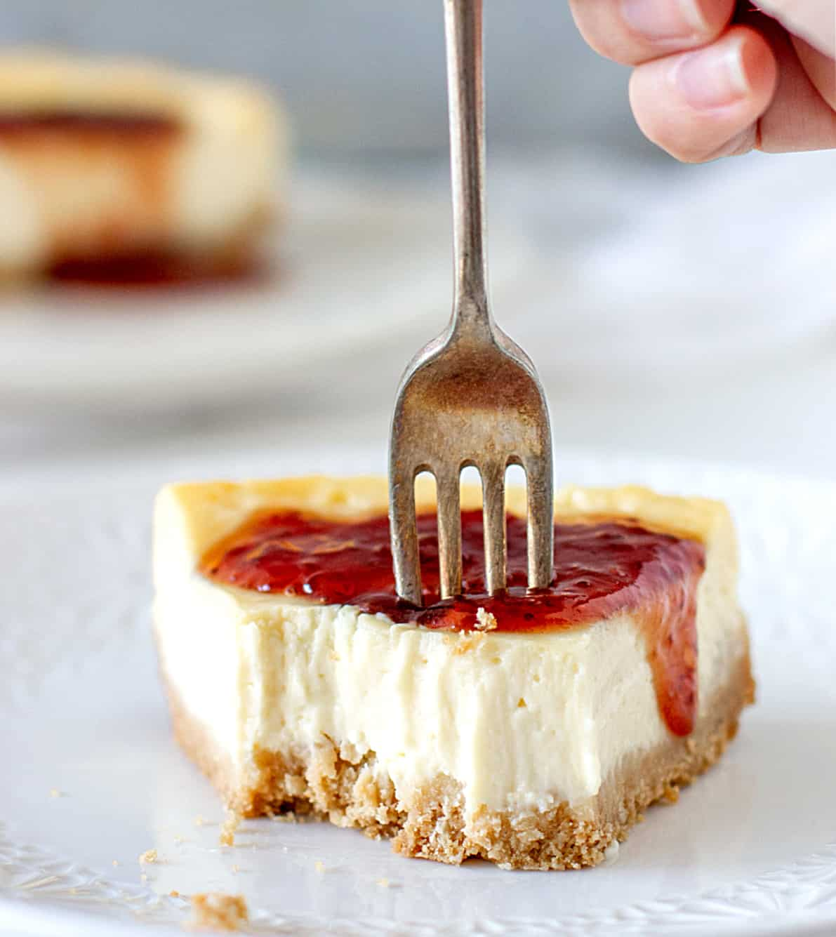 On a greyish background an eaten slice of cheesecake with silver fork coming out and red jam