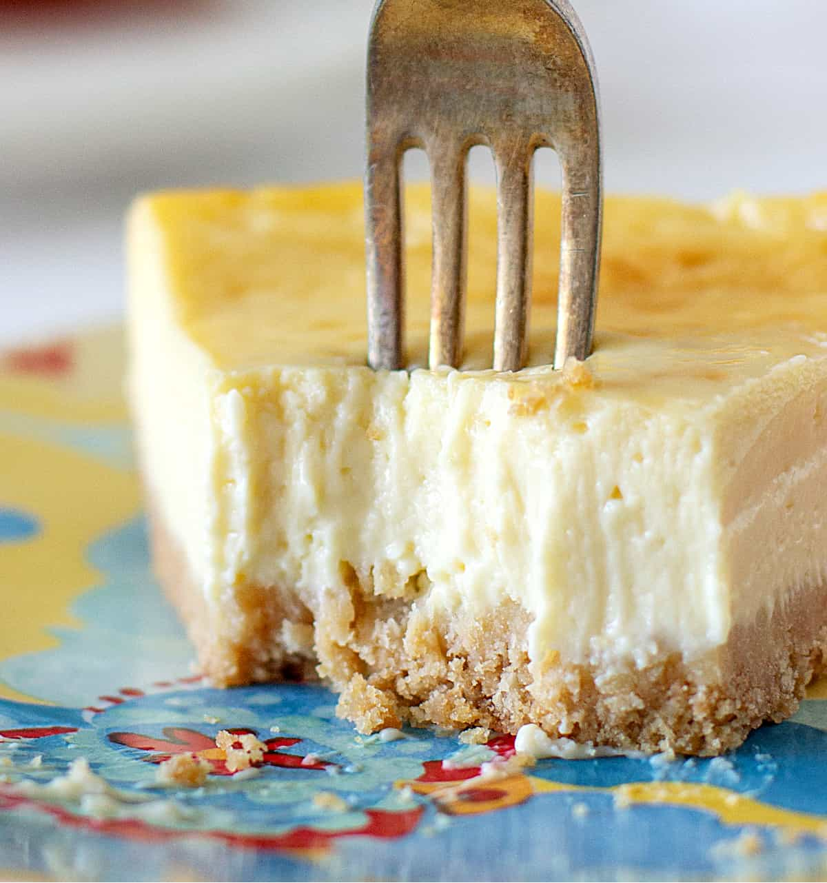 A fork plunged on a plain slice of cheesecake, colorful plate, close up image