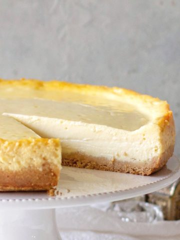 Plain cheesecake with missing slice on a white cake stand, greay background