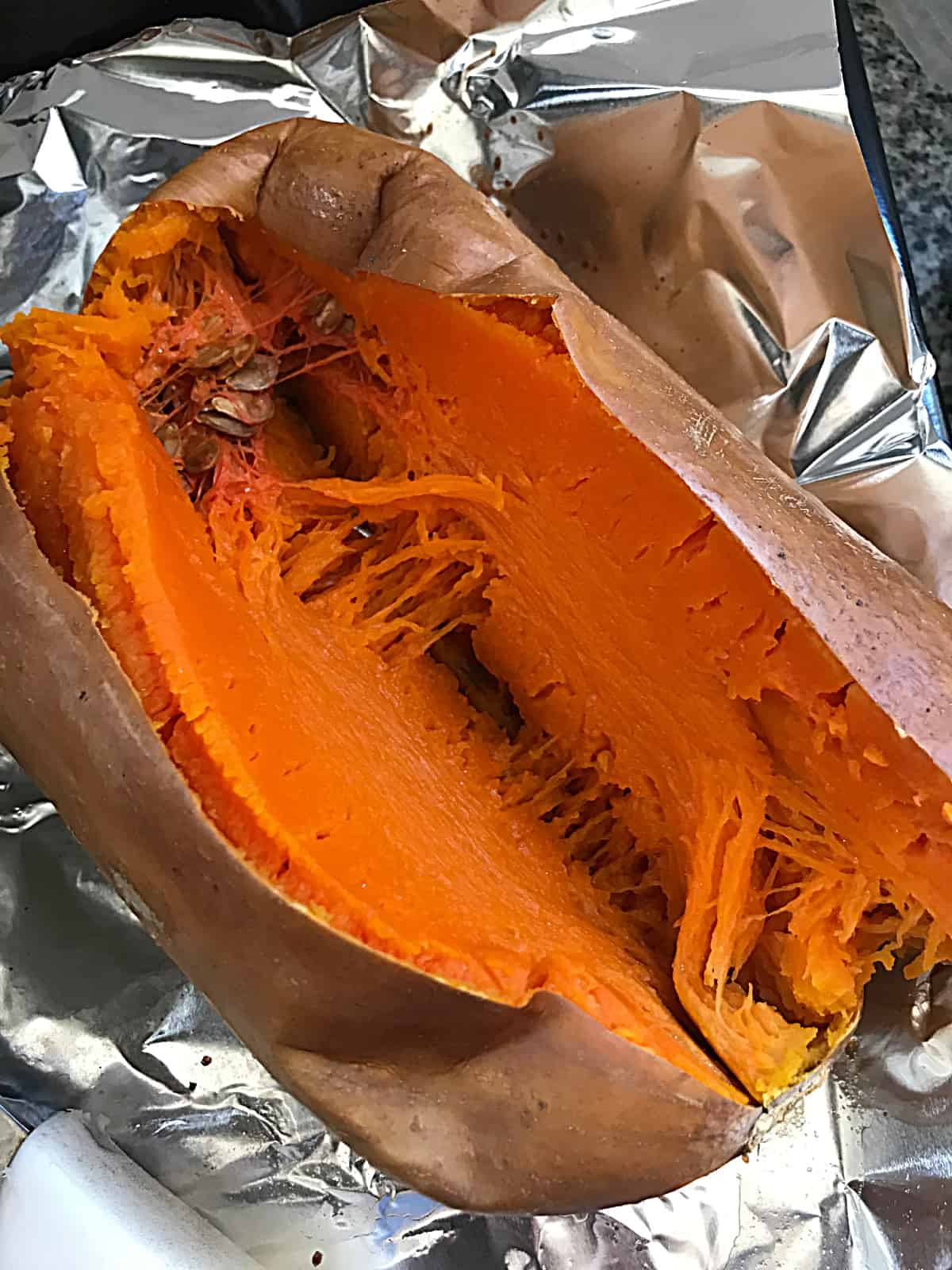 Whole baked butternut squash cut in half on a piece of aluminum paper