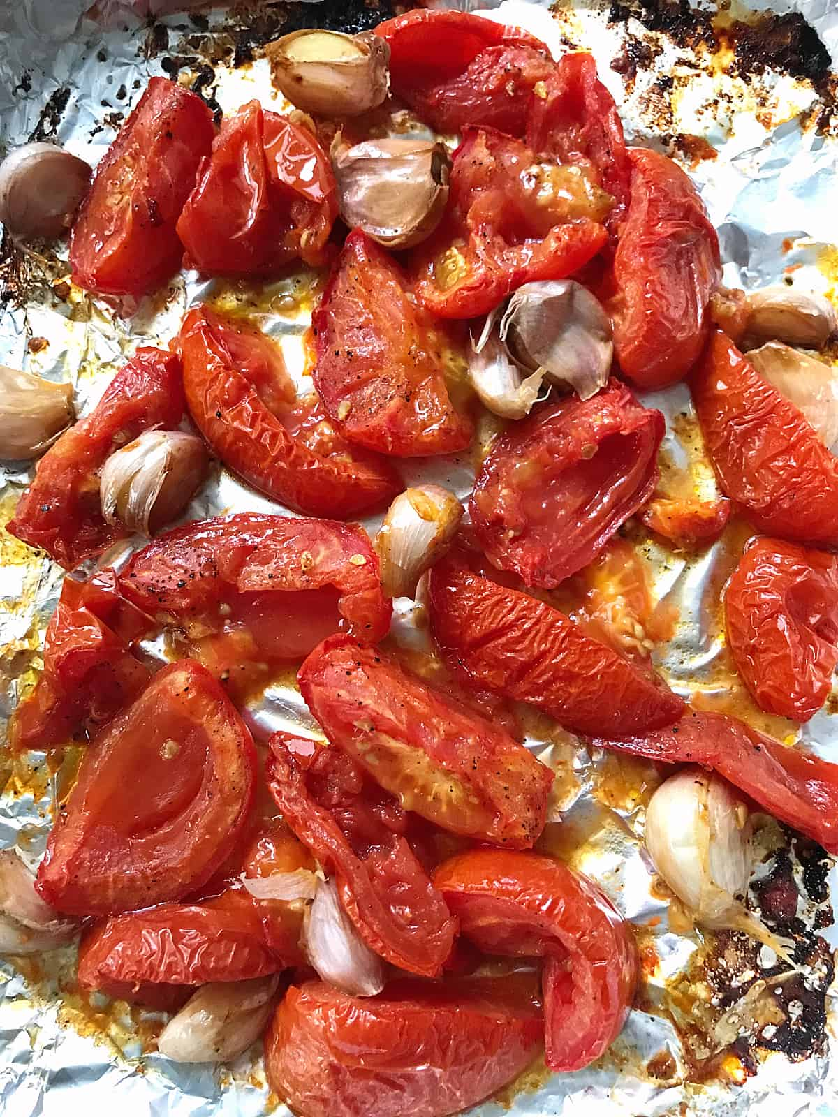 Baked tomato wedges and garlic cloves on aluminum paper