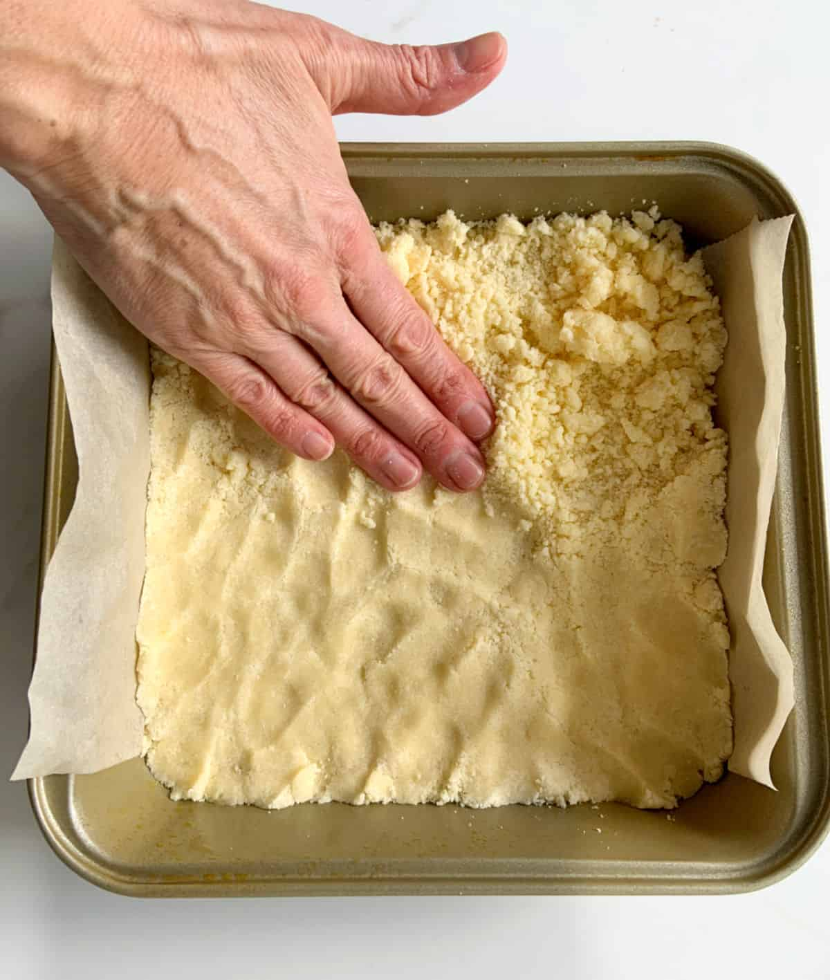 Pressing shortbread dough with hand onto bottom of square pan