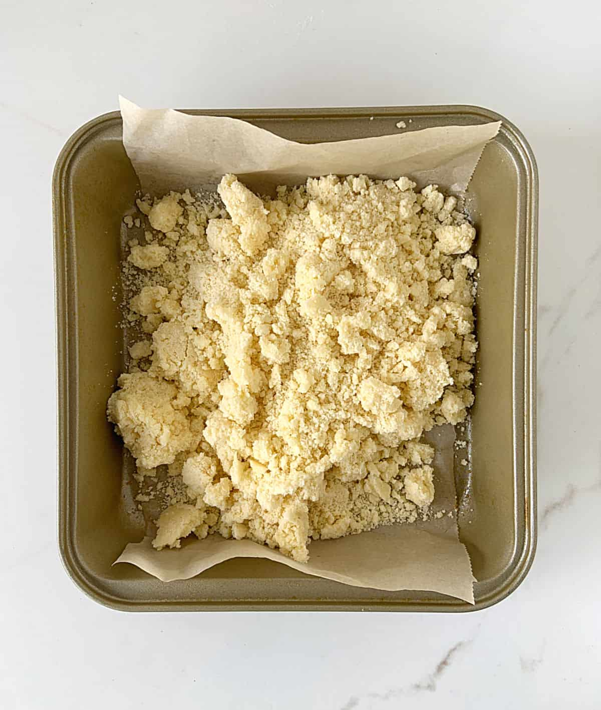 Dumped shortbread crumbly mixture on a golden pan