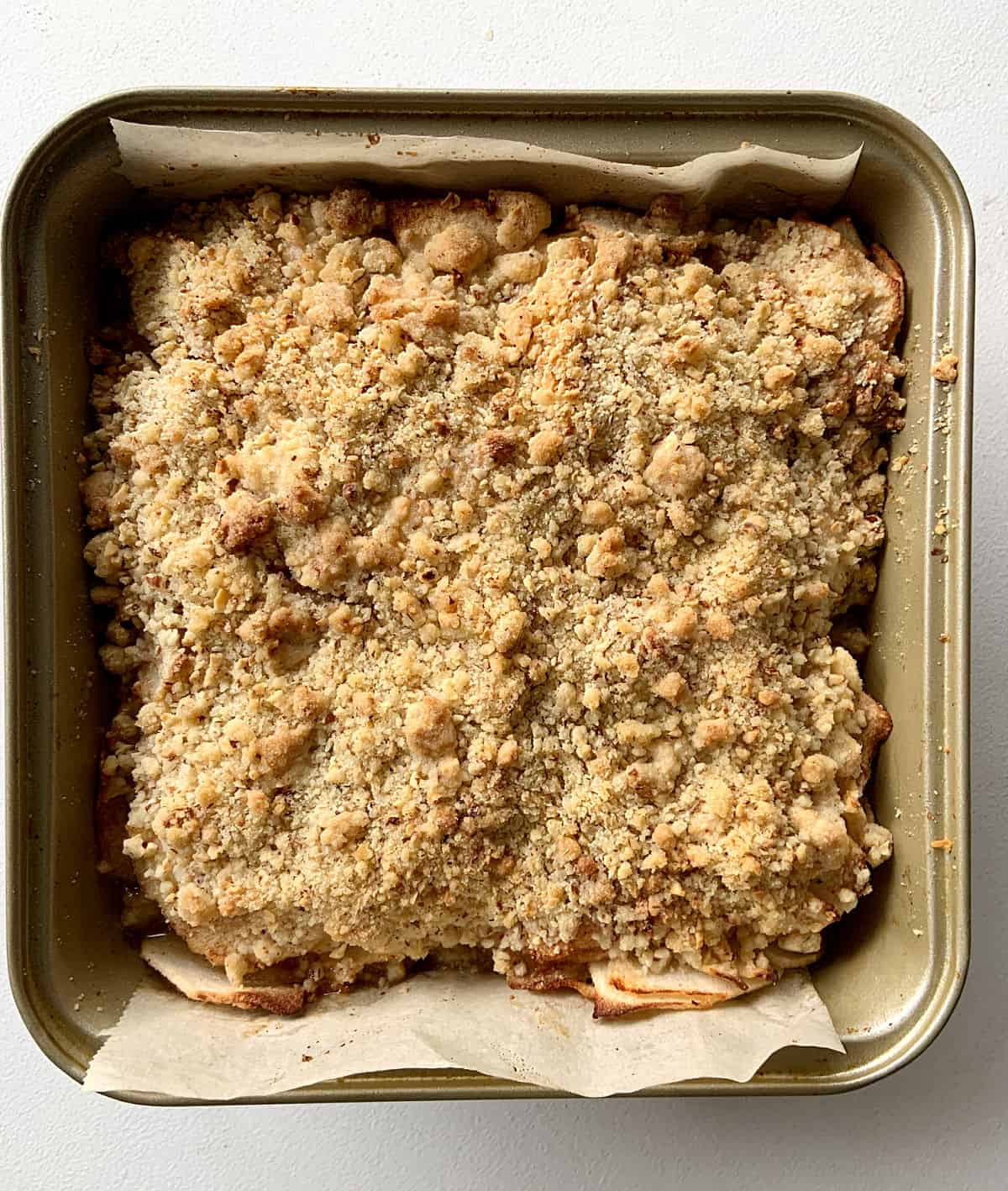 Baked apple crumb dessert in metal pan with parchment paper