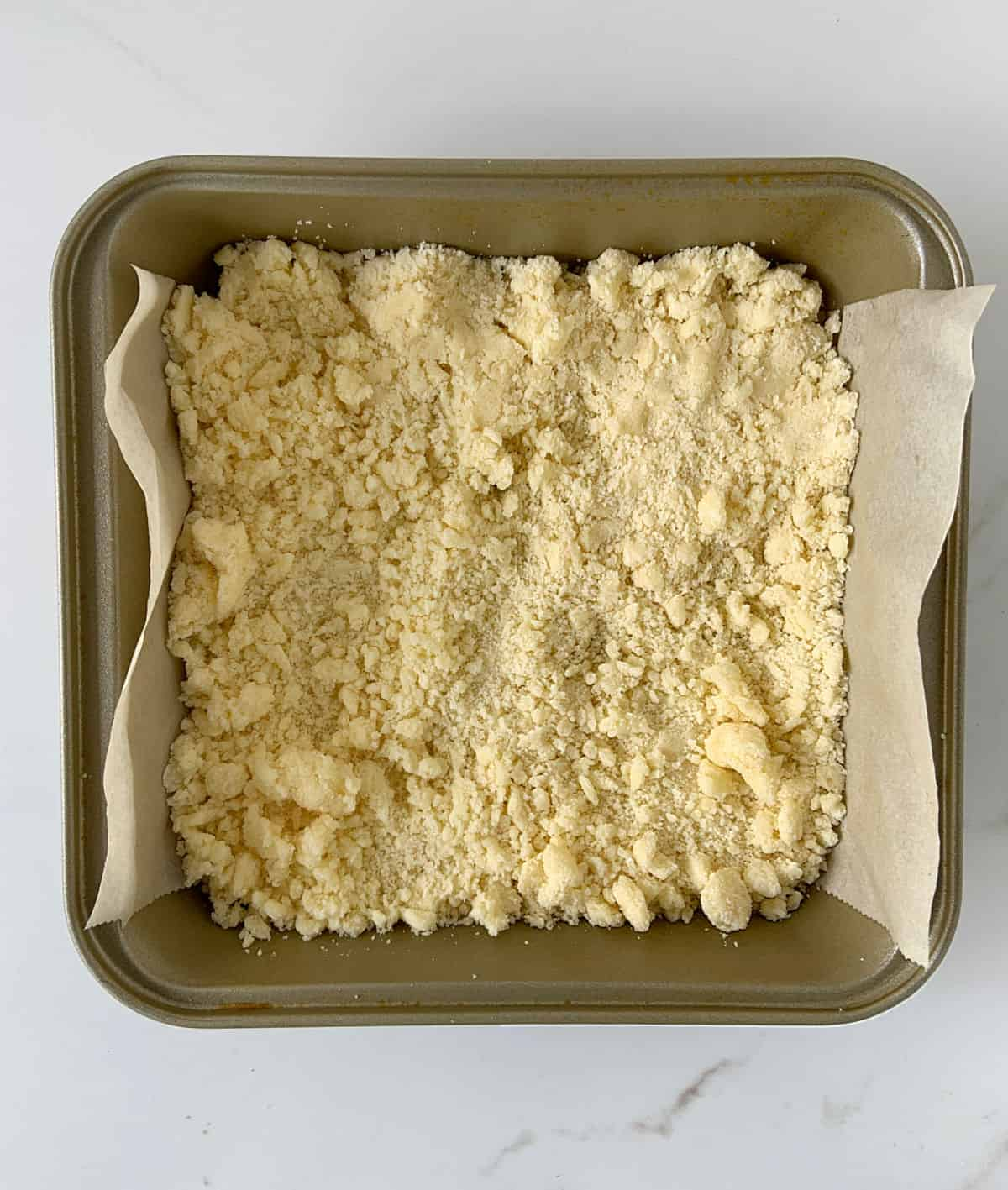 Crumbly mixture on bottom of square golden pan