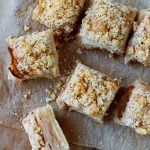 Apple crumb squares seen from the top on a thin parchment paper on a wooden board