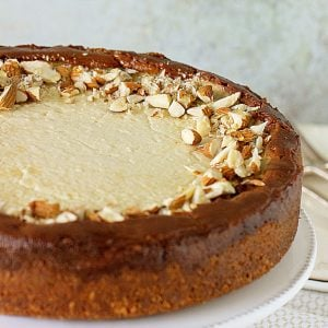 Partial view of whole cheesecake topped with almonds on white cake stand, greyish background