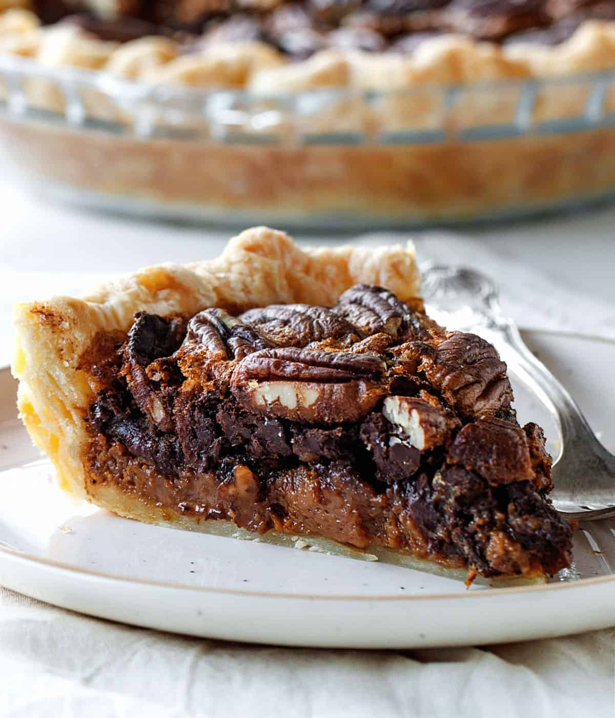 A single slice of chocolate pecan pie on white plate with fork, pie dish blurred in background