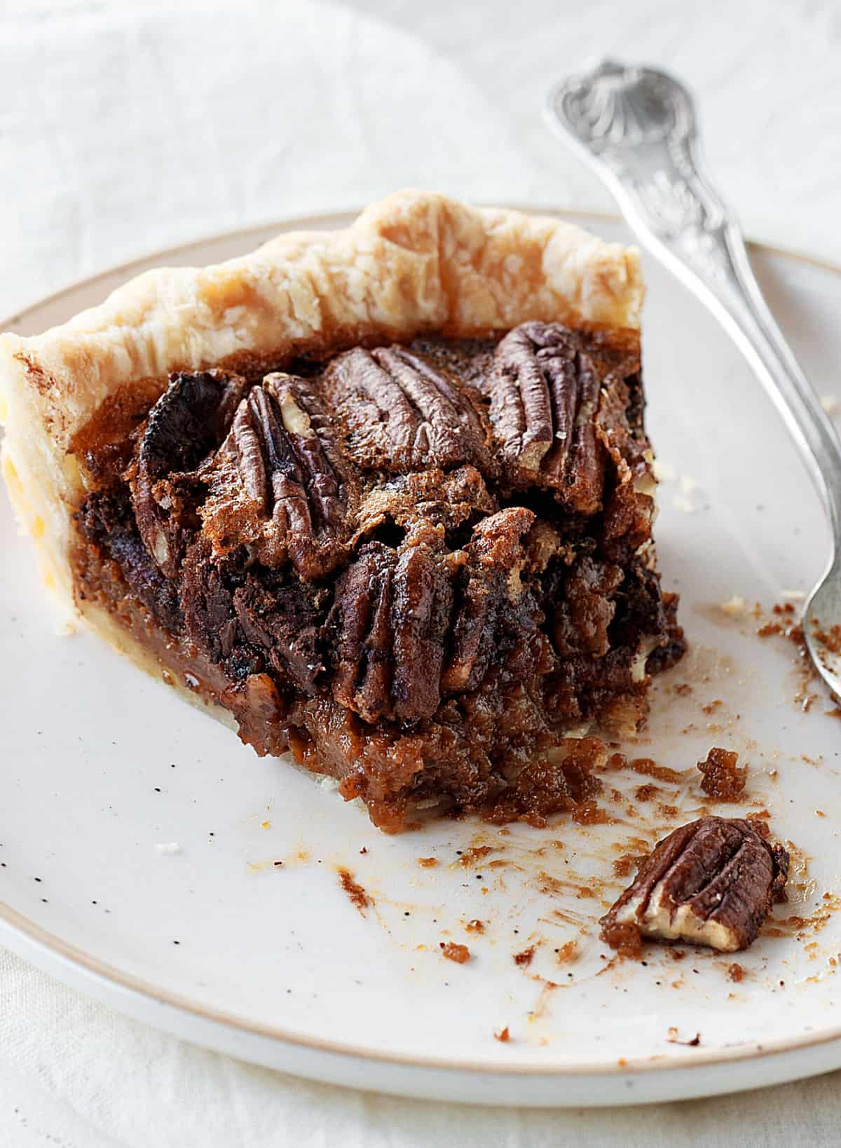 Eaten slice of pecan pie with chocolate on a whitish plate, a silver fork